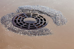 Melted water flows down through the manhole cover Stock Photos