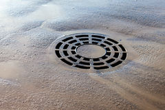 Melted water flows down through the manhole cover Royalty Free Stock Images