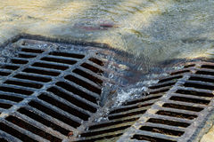 Melted water flows down through the manhole. Cover on a sunny day stock image