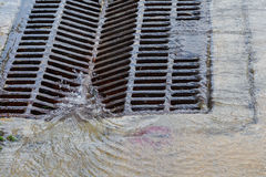 Melted water flows down through the manhole. Cover on a sunny day royalty free stock images