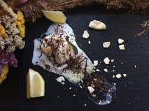 Melted white icecream with lemon on a black tray Stock Image