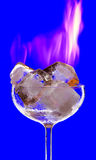 Melting. View of cocktail glass filled with burned ice on blue back Stock Photos