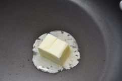 Melting Butter. Square of butter melting on a hot black frying pan royalty free stock photography