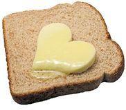 Melting butter heart. Butter heart melts on a slice of bread Royalty Free Stock Photos