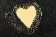 Melting butter. Heart-shaped piece of butter melting on black pan Royalty Free Stock Photography