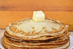 Melting butter pat on a pile of pancakes. Fried pancakes are usually roasted in all Orthodox families for the Orthodox holiday `Maslennitsa`. As a symbol of Royalty Free Stock Photography