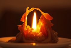 Melting candle. Weirdly shaped melting candle burning with bright flame in the darkness Stock Images