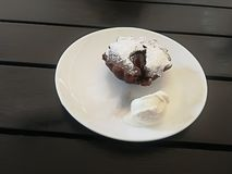 Melting chocolate fondant with ice cream on a white plate on a wooden table royalty free stock photo