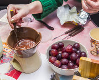 Melting chocolate to warm candles, cooking process. Chocolate fondue with fruit Stock Photo
