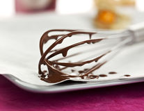 Melting chocolate on whisk Stock Photos