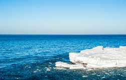 Melting ice chunks floating into blue water under empty sky. Melting chunks of ice floating out into blue water under empty sky Royalty Free Stock Photography