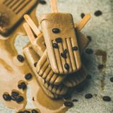 Melting coffee latte popsicles with roasted coffee beans Royalty Free Stock Images