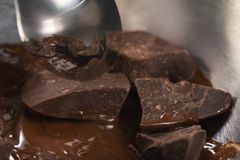 Melting dark chocolate chunks in steel bowl. Closeup Royalty Free Stock Image