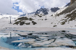 Melting glacier and the lake of clear blue water at an altitude of 2400 meters in the Alps Royalty Free Stock Image
