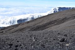 Melting glacier in midground with scree and rocks in foreground, Mount Kilimanjaro. Clear sky looking down onto clouds. Climate change Stock Photography