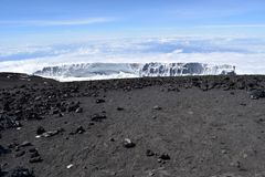 Melting glacier on Mount Kilimanjaro. With rocks and scree in foreground. Clear sky. Climate change Royalty Free Stock Image