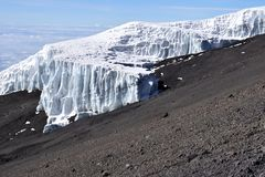 Melting glacier on Mount Kilimanjaro. With rocks and scree in foreground. Clear sky. Climate change Stock Photography