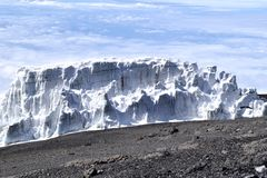 Melting glacier on Mount Kilimanjaro. With rocks and scree in foreground. Clear sky. Climate change Stock Photos