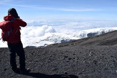 Melting glacier on Mount Kilimanjaro. With rocks and scree in foreground. Clear sky. Climate change. with trekker in foreground and some clouds below Royalty Free Stock Photo