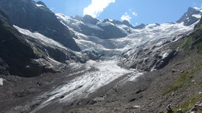 Melting glacier in the mountains. Melting Alibek glacier in the mountains Dombay. Sunny summer  day Royalty Free Stock Images