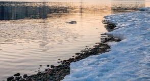 Melting ice coast at sunset stock photos