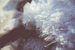 Melting the ice crystals in the spring. Transparent crystals melting ice in the spring on blurred background royalty free stock image