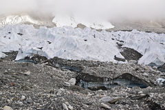 Melting ice glaciers due to global warming with thick mist at the top. This image shows flowing little stream due to the melting ice beneath the large range of royalty free stock images