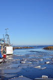 Melting ice in harbour. And parts of some fishing boats Stock Photography