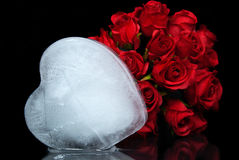 Melting ice heart with roses. Melting icy heart on a mirror with red rose bouquet Royalty Free Stock Photography
