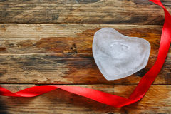 Melting ice heart. Silk red ribbon on wooden plank table Royalty Free Stock Photo