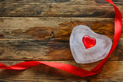 Melting ice heart, silk red ribbon. On wooden plank table, Valentine`s day background Stock Photos