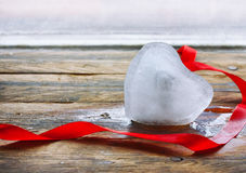 Melting ice heart about window. Melting ice heart silk red ribbon on  old wooden plank table about window Royalty Free Stock Photos
