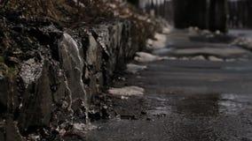 Melting ice transforms into water at walking road in spring. Melting ice transforms into water at walking road in spring season stock video