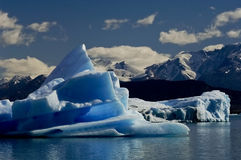 Melting iceberg from dyeing glacier drifting away Stock Photos