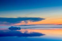 The melting iceberg on spring mountain lake in the setting sun. Stock Photo