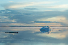 The melting iceberg on spring mountain lake in the setting sun. Royalty Free Stock Images