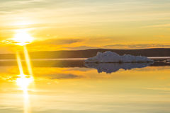 The melting iceberg on spring mountain lake in the setting sun. Royalty Free Stock Image