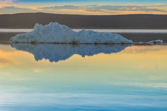 The melting iceberg on spring mountain lake in the setting sun. Royalty Free Stock Photography