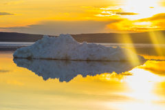 The melting iceberg on spring mountain lake in the setting sun. Stock Images