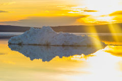 The melting iceberg on spring mountain lake in the setting sun. Stock Photo
