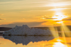 The melting iceberg on spring mountain lake in the setting sun. Royalty Free Stock Photos