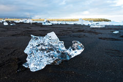 Melting of icebergs at black beach in Jokulsarlon glacier lagoon Royalty Free Stock Photos