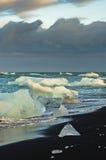 Melting of icebergs at black beach in Jokulsarlon glacier lagoon Royalty Free Stock Photo