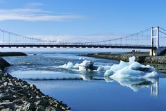 Melting icebergs on Jökulsarlon glacier lagoon approaching the sea, bridge reflecting in the water stock images