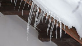 Melting Icicles hanging on old house roof stock footage