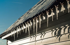 Melting icicles on the roof. Stock Photo