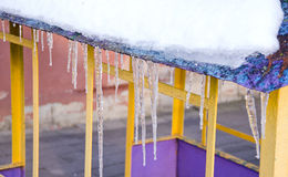Melting icicles spring on roof playground house. Stock Image