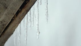 Melting icicles in the spring under the roof. Spring melting of ice. Melting icicle shimmers in the sun. Thaw, the off-season, late winter, early spring stock video