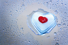 Melting icy heart. Heart of ice melting on the surface, water drops Royalty Free Stock Images