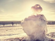 Melting icy snow manin landscape. People walk. In winter sunny day around. Holes in snowman body woods wild weather water trunk traditional symbol sunset royalty free stock photography
